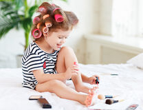 Happy funny child girl with hair curlers does a pedicure, paints Royalty Free Stock Photography