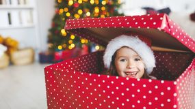 Happy funny child girl hiding in big christmas present gift royalty free stock photos