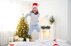 Happy child girl jumping in bed on Christmas morning. Happy funny child girl  jumping in bed on Christmas morning Royalty Free Stock Image