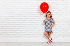 Happy funny child girl with  red ball near an brick wall Royalty Free Stock Image