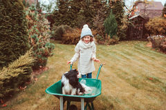 Happy funny child girl riding her dog in wheelbarrow in autumn garden, candid outdoor capture Royalty Free Stock Photos