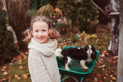 Happy funny child girl riding her dog in wheelbarrow in autumn garden, candid outdoor capture Stock Photography