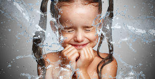 Happy funny child girl in  spray of water laughs Stock Photography