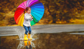Happy funny child girl with umbrella jumping on puddles in rubb stock images