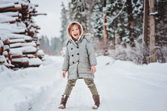 Happy funny child girl on the walk in winter snowy forest Royalty Free Stock Photography