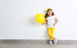 Happy funny child girl with yellow balloon near an empty wall royalty free stock images