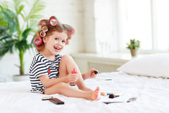 Happy funny child girl with hair curlers does a pedicure, paints royalty free stock images