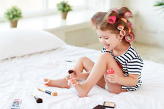 Happy funny child girl with hair curlers does a pedicure, paints Stock Image