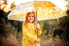 Happy funny child with umbrella under the autumn shower. royalty free stock image