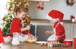 Happy children bake christmas cookies. Happy funny children bake christmas cookies royalty free stock image