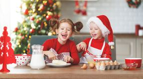 Happy children bake christmas cookies. Happy funny children bake christmas cookies stock photo