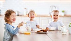 Happy funny children eating breakfast Stock Image