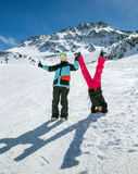 Happy couple in mountains. Happy funny couple on the background of snowy mountains. Standing upside down and showing OK sign Royalty Free Stock Image