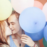 Happy and funny couple kissing at background of color balloons Stock Photos