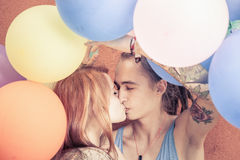 Happy and funny couple kissing at background of color balloons Stock Images