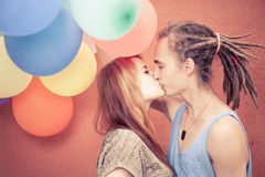 Happy and funny couple kissing at background of color balloons Stock Photo