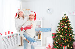 Happy funny couple plays fool and having fun on Christmas at home. Happy funny cheerful family couple plays the fool and having fun on Christmas at home royalty free stock photo