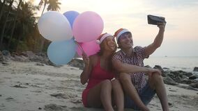 Happy funny couple sit on the beach with multicolored balloons on Christmas travel holidays taking selfie picture with. Happy beautiful couple on Christmas stock footage