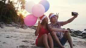 Happy funny couple sit on the beach with multicolored balloons on Christmas travel holidays taking selfie picture with. Happy beautiful couple on Christmas stock video footage