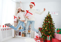 Happy funny family couple jumping and having fun on Christmas at Stock Photography