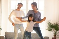 Happy family and child daughter laughing dancing in living room stock image
