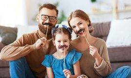 Happy funny family mother father and child daughter with mustache on stick stock images