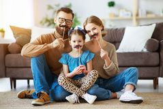 Happy funny family mother father and child daughter with mustache on stick stock photography