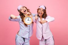 Happy funny friends women in pajamas holding alarm clock. Photo of two happy funny friends women in pajamas isolated over pink background holding alarm clock stock photography