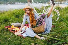 Happy funny girl in blue dress and hat with flowers, enjoying picnic