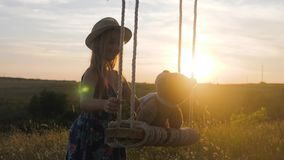 Happy funny girl in hat is playing with a teddy bear on a rope swing during sunset. Kid playing on the nature outdoors. Beautiful rays of the sun. Childhood stock video