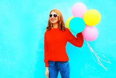 Happy funny girl holds a colorful air balloons on a blue Stock Image