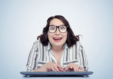 Happy funny girl programmer in glasses with keyboard in front of computer Stock Photo