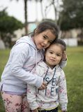 Happy funny girl twins sisters hugging and laughing stock photos