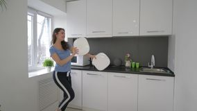 Happy funny housewife woman fooling around and sings with dishes in arms at cuisine at home stock video footage