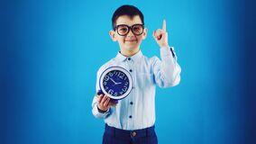 Happy funny kid with clock on a blue background.