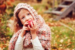 happy funny kid girl in cozy knitted scarf eating fresh apple in autumn garden Stock Photos
