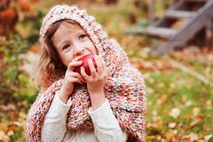 Happy funny kid girl in cozy knitted scarf eating fresh apple in autumn garden stock photo