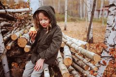 Happy funny kid girl eating fresh apple in autumn forest royalty free stock image