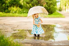 Happy funny kid girl with umbrella jumping on puddles in rubber boots and in dress and laughing. Happy funny kid girl with umbrella jumping on puddles in rubber stock photo