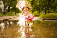 Happy funny kid girl with umbrella jumping on puddles in rubber boots and in dress and laughing. Happy funny kid girl with umbrella jumping on puddles in rubber royalty free stock photography