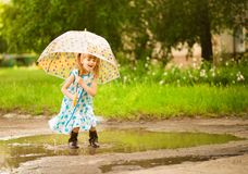 Happy funny kid girl with umbrella jumping on puddles in rubber boots and in dress and laughing stock photos