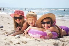 Happy funny kids on beach. Happy funny kids laying on sand beach stock image