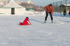 Happy funny kids playing hockey at the rink. In the winter. A child with a stick on the ice skating in the winter walks on the street Royalty Free Stock Photos