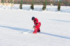 Happy funny kids playing hockey at the rink. In the winter. A child with a stick on the ice skating in the winter walks on the street Stock Images