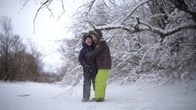 The happy and funny kids standing under the tree from which the snow falls. Two guys smiling and genuinely happy. The stock video