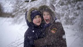 The happy and funny kids standing under the tree from which the snow falls. Two guys smiling and genuinely happy. The stock footage