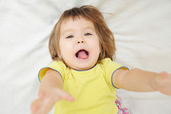 Happy funny little girl with hands up lying on bed Stock Image