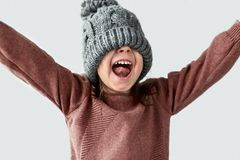 Happy funny little girl hidden the eyes in winter warm gray hat, joyful smiling with hands wide open and wearing sweater isolated. On a white studio background royalty free stock image