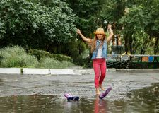 Happy funny little girl jumping on puddles in rubber boots and laughing stock photo