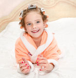 Happy funny little girl with manicure and hair curlers Royalty Free Stock Photography